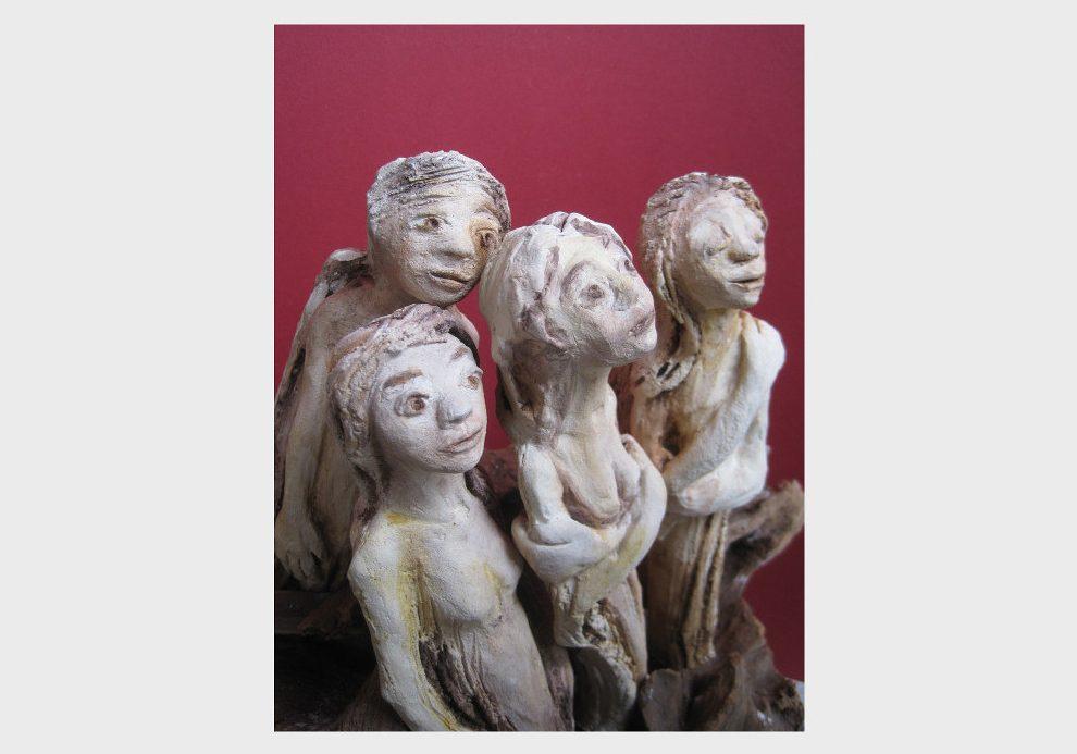 Skulpturen in erdfarben auf Wurzel: Frauen