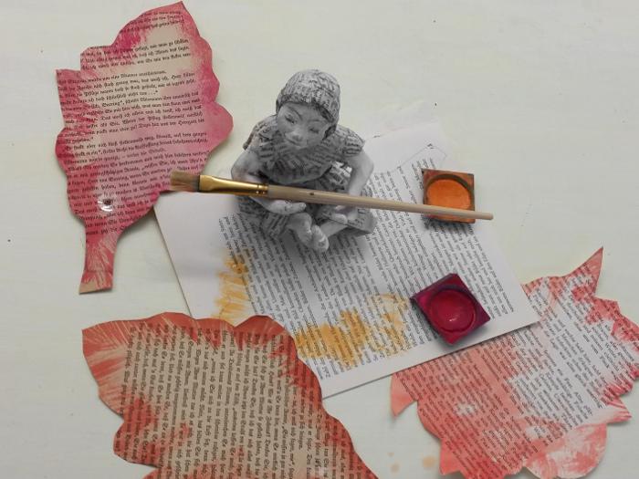 Buchseiten und Baumblätter mit Wasserfarben in warmen Farben bemalen. Bastel Anleitung für eine Girlande aus alten Buchseiten.